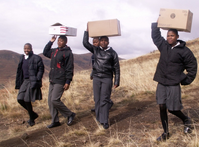 Lesotho children carrying their new library the last leg of the journey.